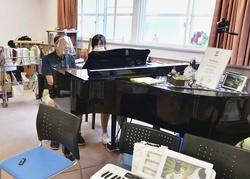 グランドピアノの伴奏で歌う安達春雄さん(左)=京都市伏見区の京都医療センター