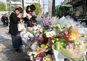 乗用車が暴走し、母子が死亡した事故現場付近で手を合わせる家族=20日午後、東京都豊島区