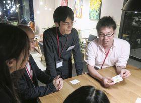 オフィス向けの玩具発表会で、カードゲームを楽しむ参加者=5月7日、東京都千代田区