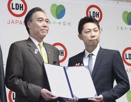 締結式で撮影に応じる長野県の阿部守一知事(左)とEXILEのUSAさん=20日午後、長野県庁