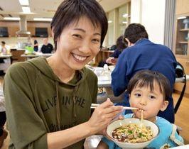 沖縄そばのルーツとなった110年前の味を再現した「唐人そば」を試食し、笑顔を見せる親子=15日、那覇市西の県男女共同参画センターてぃるる