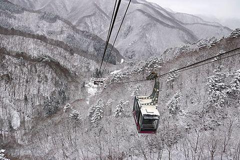 天元台高原の湯元駅と高原駅を結ぶロープウエーの窓からは、うっすらと雪化粧した山々が広がっていた=米沢市