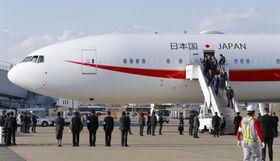 羽田空港に駐機する新政府専用機。外遊から帰国した安倍首相夫妻(右側のタラップ中央)が機内に入って視察した=20日午後