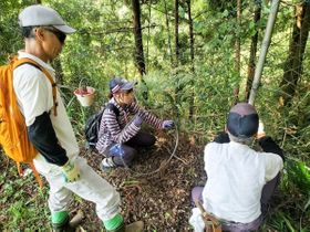 大山地区の山中で、鳥獣被害から農作物を守るための柵を補修する学生(中央)ら=9月27日