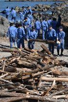 流木などの漂着ごみを集める生徒たち=16日午前、八戸市の蕪島海浜公園