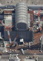 使用済み核燃料プールから搬出のため、東京電力福島第1原発3号機(上)から出発する燃料を載せたとみられるトレーラー(中央下)=23日午前11時20分(共同通信社ヘリから)