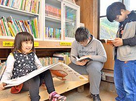 新しくなった本棚の前で絵本や漫画などを読む子どもたち