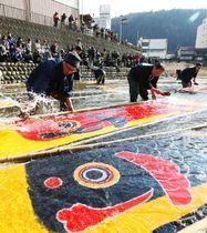 こいのぼりを清流にさらし、職人らがのりを洗い流す「寒ざらし」が行われた=20日午後、岐阜県郡上市