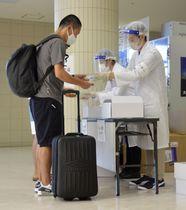 PCR検査の検体採取キットを受け取る乗客(左)=11日午前、東京都港区の竹芝客船ターミナル