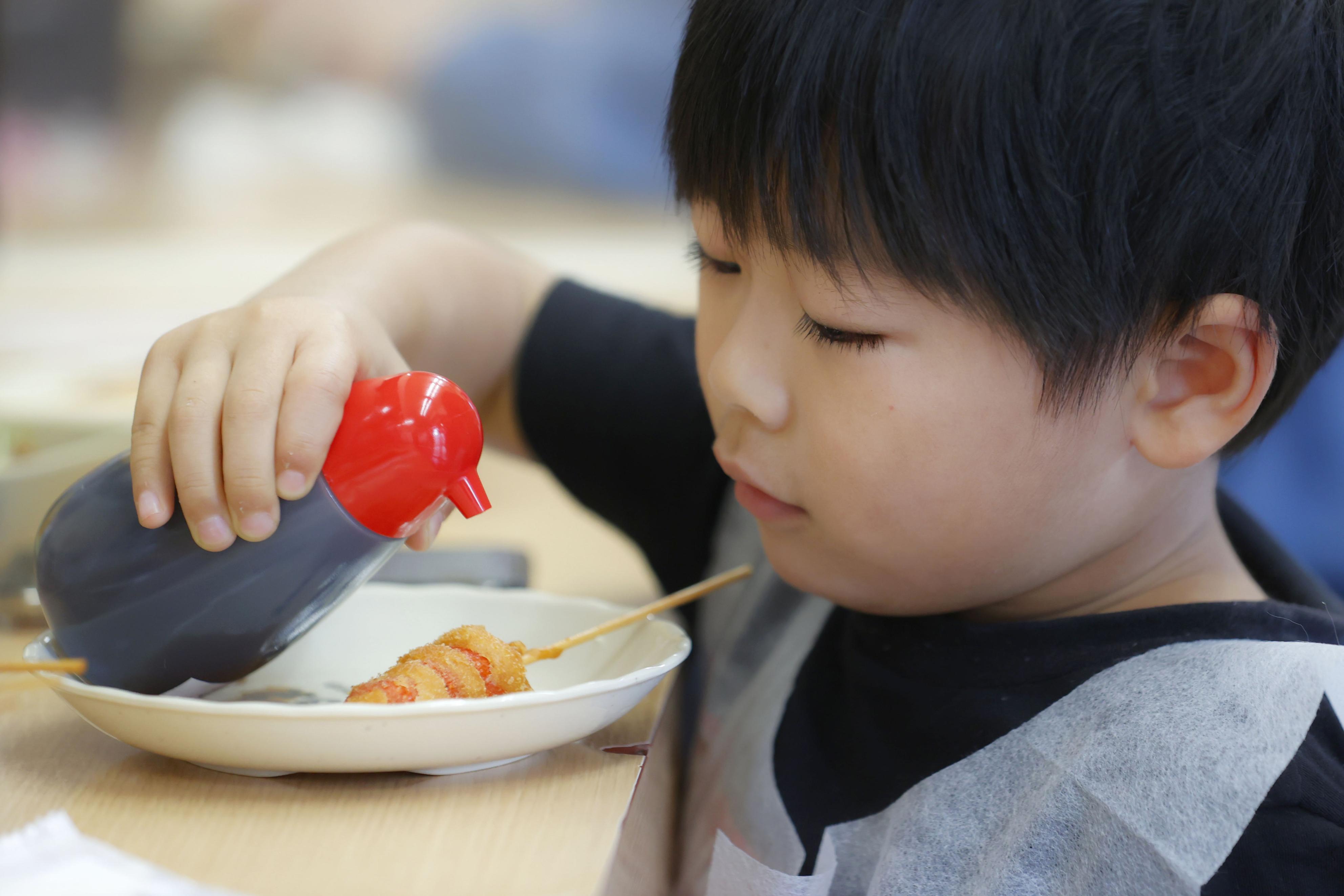 串カツにソースをかける男の子=20日、大阪・新世界の「串かつだるま通天閣店」