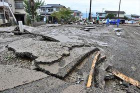 濁流や浸水で剥がれたとみられるアスファルト舗装=14日午後1時5分ごろ、伊達市梁川町