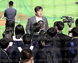 グラウンドに入り、野茂さん(中央)から話を聞く生徒
