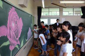 笑顔で黒板アートに見入る中居林小の児童