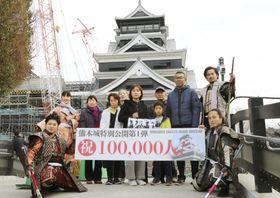 熊本城の見学再開から通算10万人目の来場者となり、記念撮影する池末羚くん(中列右から3人目)ら=14日午前、熊本市