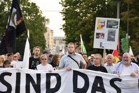 「われわれが国民だ」と書かれた横断幕を手に、難民排斥を訴える右派のデモ隊=2019年8月、ドイツ東部ケムニッツ(共同)
