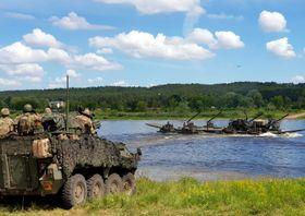 NATOの演習「サーベル・ストライク」で川を渡る部隊=13日、リトアニア(ロイター=共同)