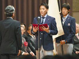 ジャカルタ・アジア大会の日本選手団結団式で、決意表明する主将で陸上男子の山県亮太(中)。右は旗手でソフトボール女子の上野由岐子=東京都港区で