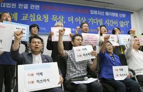 23日、三菱重工業の資産売却申請について韓国・光州で記者会見し、拳を掲げる元徴用工らの訴訟の原告側(共同)