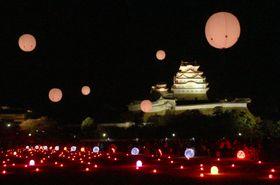 世界遺産・姫路城で始まった、照明を使った芸術作品で飾るイルミネーションイベント。LED電球が敷き詰められ、光るバルーンが浮かぶ=10日夜、兵庫県姫路市