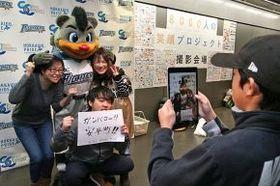 被災地へのメッセージを手にした笑顔の観客を撮影する早来小の児童(右)=金田淳撮影