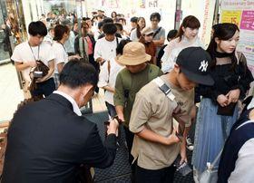 開業15周年を迎え、来店者にバウムクーヘンをプレゼントする日高淳一社長(左)ら=鹿児島市中央町
