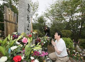 「御巣鷹の尾根」にある「昇魂之碑」に献花し、手を合わせる日航の植木義晴社長=12日午後、群馬県上野村(代表撮影)