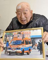 花車としても活躍した宣伝カーの記念写真を抱え、思い出を語る野田忠幸さん