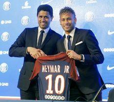 サッカーのフランス1部リーグ、パリ・サンジェルマンに移籍し、入団会見で背番号「10」のユニホームを手にするネイマール選手(右)=4日、パリ(AP=共同)