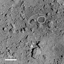 探査機はやぶさ2が小惑星りゅうぐうの上空約500メートルで撮影した表面の人工クレーター。実線で囲まれた部分が、人工クレーターの中心部分となる円形の領域、点線部分がくぼんだ領域(JAXA提供)