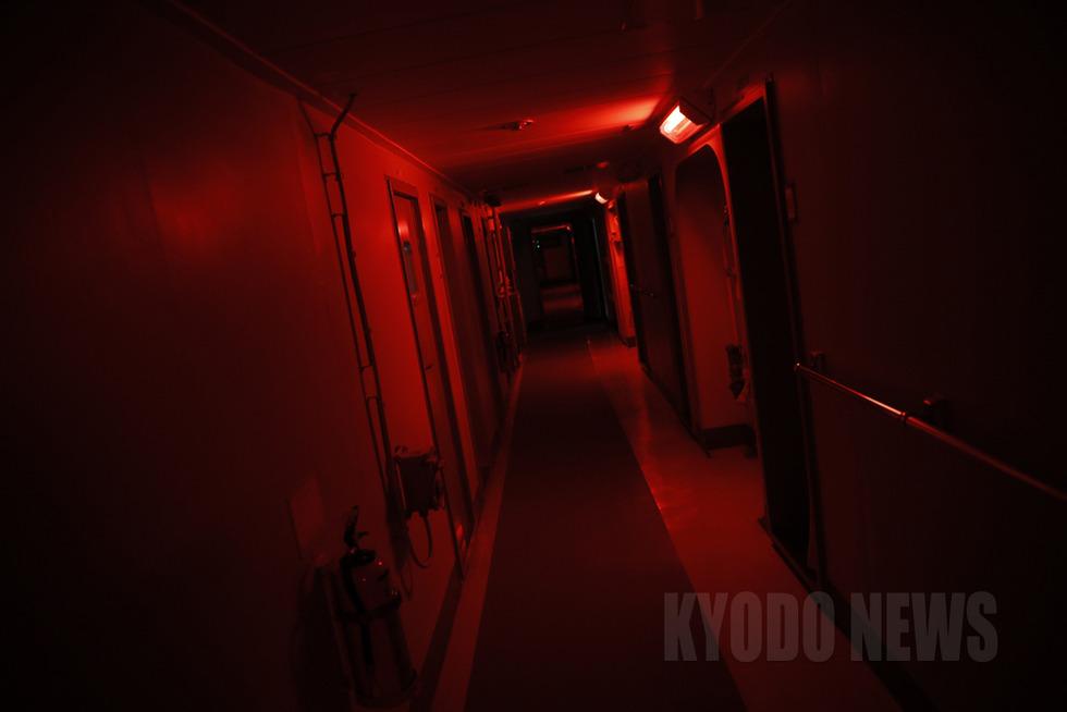 赤色灯だけがともる早朝の「しらせ」の廊下。