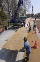 東京五輪マラソン・競歩の運営施設設置に向け、大通公園の通路に鉄板を敷く工事関係者=12日午前10時5分、札幌市中央区大通西4(大石祐希撮影)