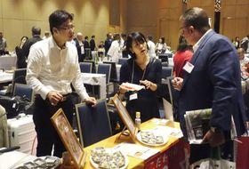 オーストラリア・シドニーの日本食材商談会で、グルテンフリーの豆腐ハンバーグなどをアピールする三忠の渡辺至誠社長(左)=16日(共同)