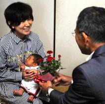 枝広市長(右)からバラを受け取る暖ちゃんと茜さん