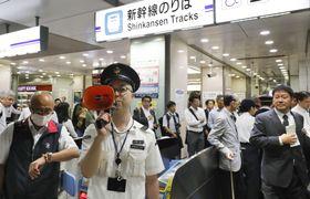 地震の影響で新幹線が運転を見合わせ、混雑するJR名古屋駅の改札口付近で対応する駅員=18日午前