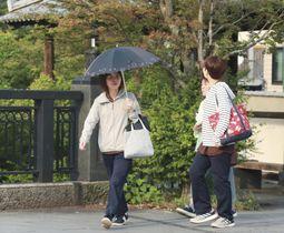 今年初めての猛暑日となった大分県竹田市で、日傘を差して歩く女性=25日午後