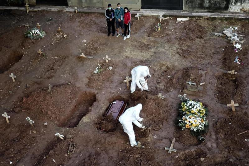 8日、ブラジル・リオデジャネイロの墓地で、新型コロナウイルスの死者を追悼する遺族(ゲッティ=共同)