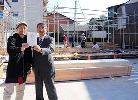 オープンを2日後に控え、急ピッチで建設が進む「新大宮広場」で、マルシェへの来場を呼びかけるプロジェクトメンバー(京都市北区紫竹西桃ノ本町)