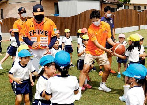 園児とボール遊びで交流する県内プロスポーツ選手ら=11日午後、伊予市米湊