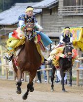 加茂神社の参道を人馬一体となり疾走する「お供馬の走り込み」=20日午前、今治市菊間町浜