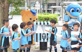 ユニホーム柄に新調されたポストに手紙を投函する子どもたち =川崎市中原区