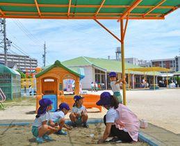 首まで覆う帽子をかぶり、日陰で遊ぶ園児たち=愛知県豊明市の名古屋短期大付属幼稚園で