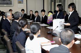 19日、ジュネーブの軍縮会議日本政府代表部を訪れた高校生平和大使ら。高見沢将林軍縮大使(左端)に千羽鶴を手渡した(共同)