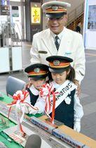 鉄道模型の展示コーナーでテープカットをする園児と前川駅長=高松市浜ノ町、JR高松駅