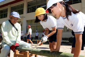 上垣さん(左)の助言を受けて竹を切る友和小の児童