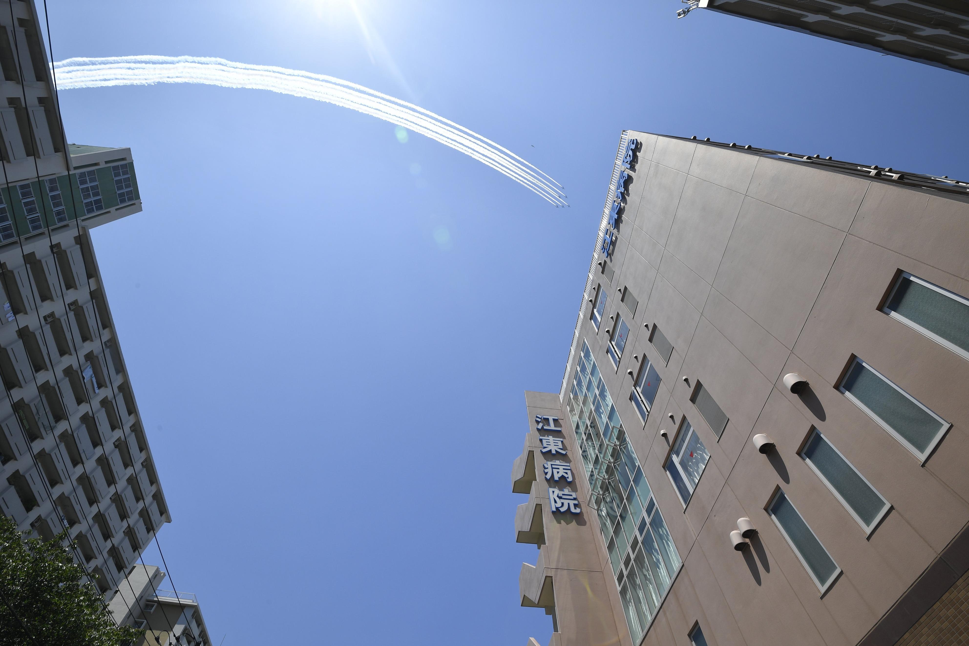 医療従事者に敬意を示すため、東京都江東区の江東病院上空を飛行する航空自衛隊のブルーインパルス=29日午後