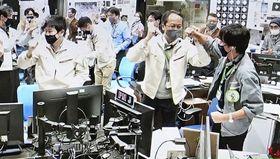 はやぶさ2のカプセル分離後、本体の軌道変更に成功し、管制室で喜ぶJAXAの津田雄一教授(手前右から2人目)ら関係者の映像=5日午後、相模原市