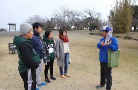 地元ガイド(右)の説明を聞く家族連れの観光客=南島原市、原城跡