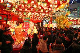 色とりどりの光に包まれ、観光客らでにぎわう会場=長崎市新地町、湊公園