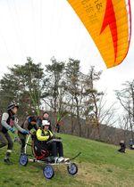 専用車いすを使い、パラグライダーの1人乗り飛行に挑む加藤健一さん=南陽市・南陽スカイパーク