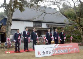 金栗四三生家記念館の開館式典でテープカットする関係者=11日午前、熊本県和水町